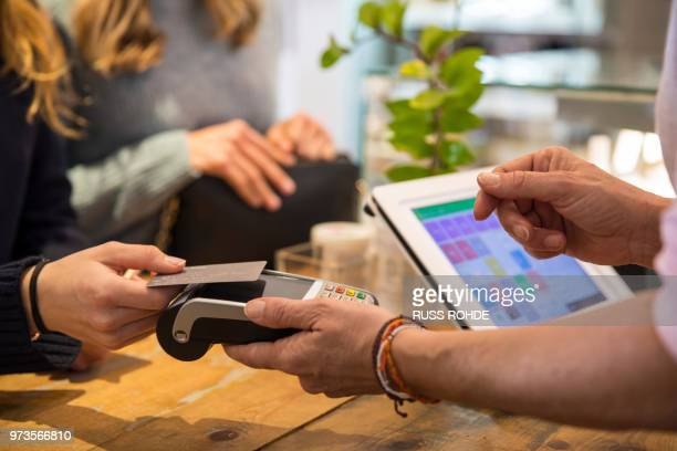 female customer in shop, paying for goods using credit card on contactless payment machine, mid section, close-up - comodidad fotografías e imágenes de stock
