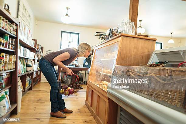 female customer leaning to look at display cabinet in country store - heshphoto stock pictures, royalty-free photos & images