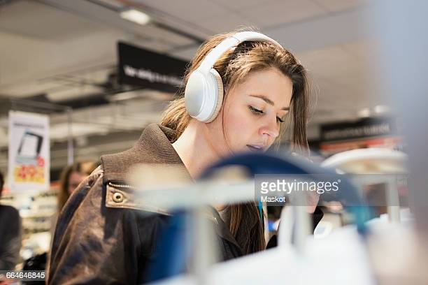 Female customer listening headphones at electronics store
