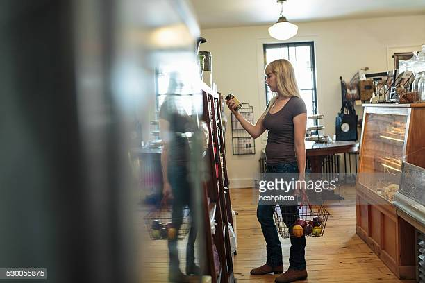 female customer looking at tin can in country store - heshphoto foto e immagini stock
