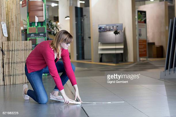 female customer measuring floor tiles in hardware store - sigrid gombert stock pictures, royalty-free photos & images
