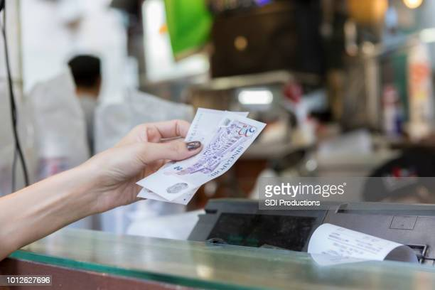 Female customer pays for purchase in outdoor market
