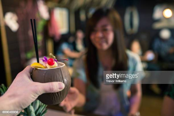 Female customer receiving a drink in a tropical themed restaurant or bar