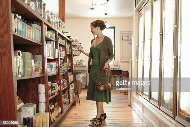 female customer selecting from shelf in country store - heshphoto stock pictures, royalty-free photos & images