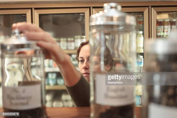 female customer selecting jar from shelf in country store - heshphoto stock pictures, royalty-free photos & images