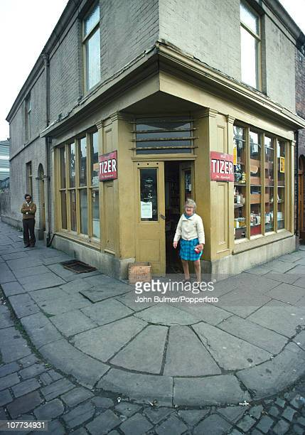 A female customer stands beside advertisements for Tizer outside a corner shop in Manchester England in 1976