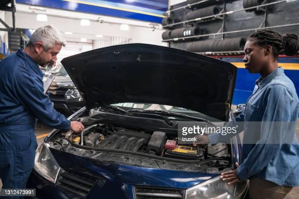 cliente mulher falando com mecânico de carros - izusek - fotografias e filmes do acervo