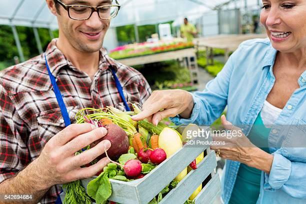 Feminino cliente conversações com agricultor sobre produtos orgânicos