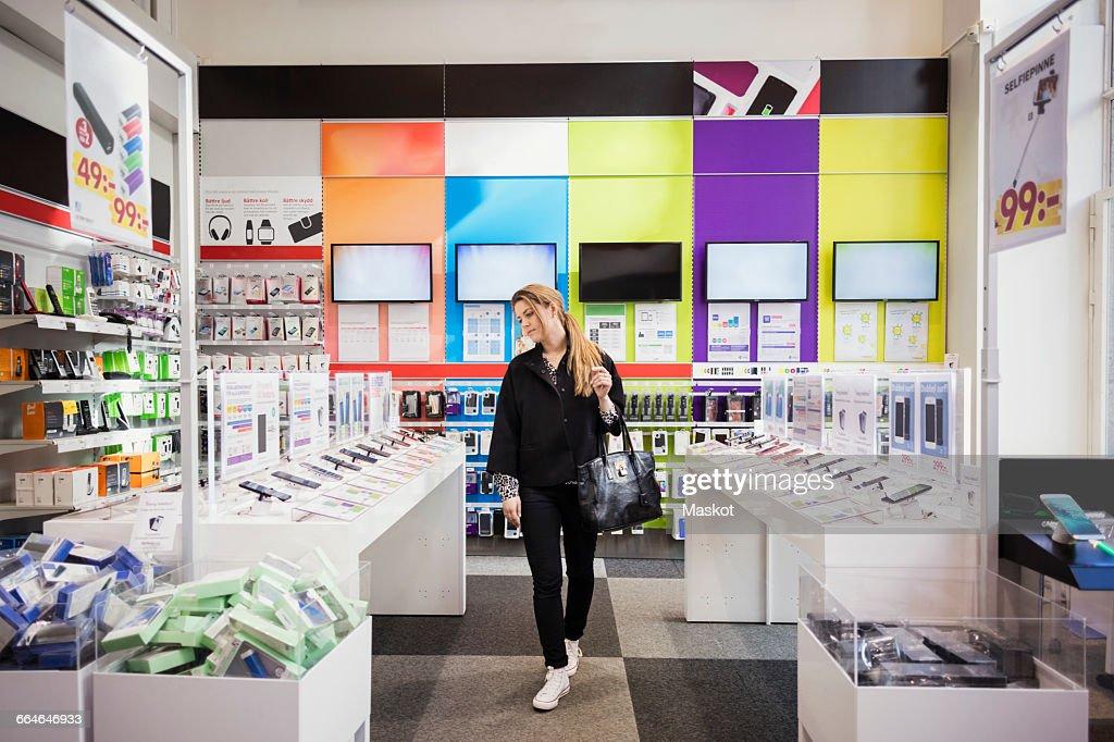 Female customer viewing smart phones in store : Stock Photo