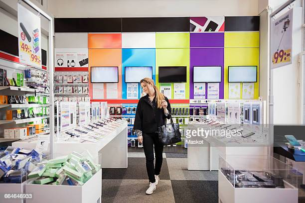 female customer viewing smart phones in store - electronics store stock photos and pictures