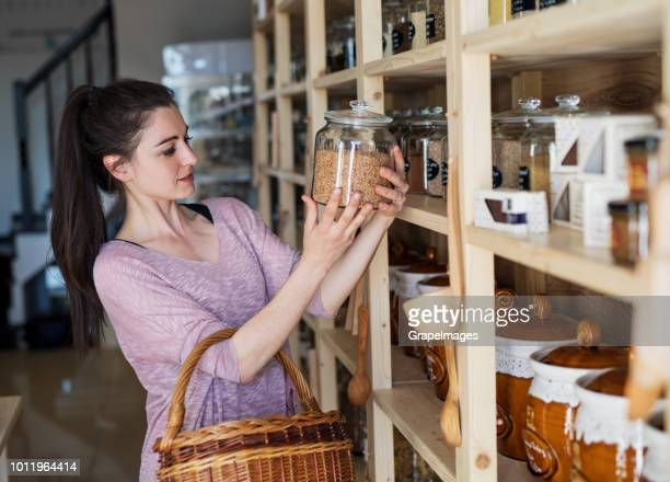 Eine Kundin mit einem Korb in einem Null-Abfall-Geschäft.