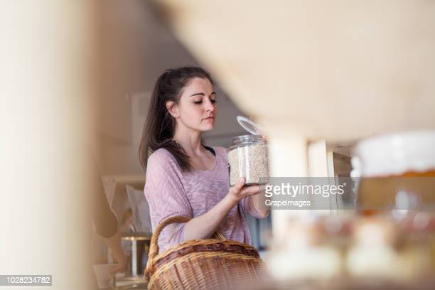 a female customer with a basket in a zero-waste store. - rice food staple stock pictures, royalty-free photos & images