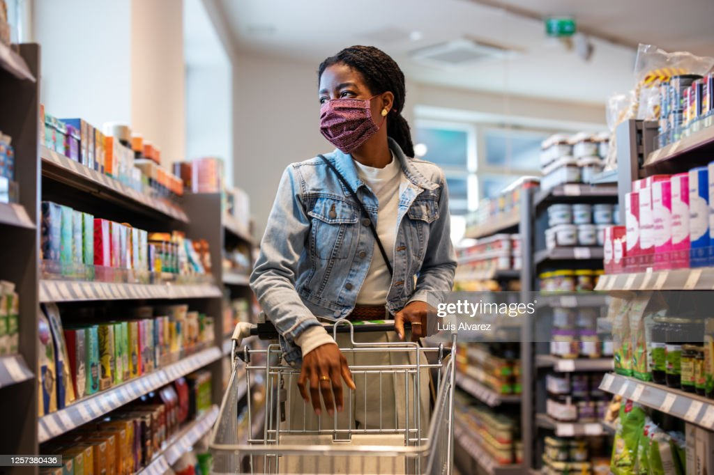 Female customer with face mask shopping at a grocery store : Stock Photo