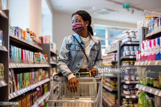 female customer with face mask shopping at a grocery store - merchandise stock pictures, royalty-free photos & images