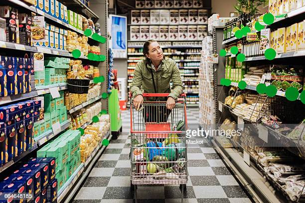 Female customer with shopping cart on alley at supermarket