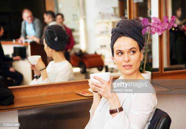 female customer with towel around hair and coffee cup in hair salon - 美容室 椅子 ストックフォトと画像