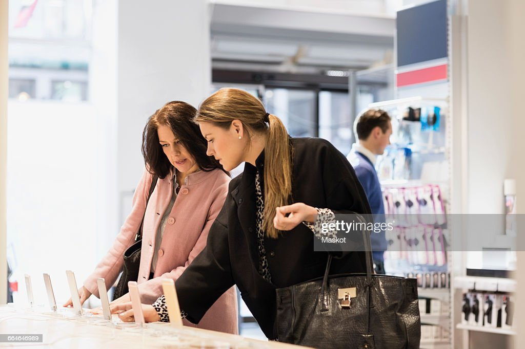 Female customers are using smart phones in showroom : Stock Photo