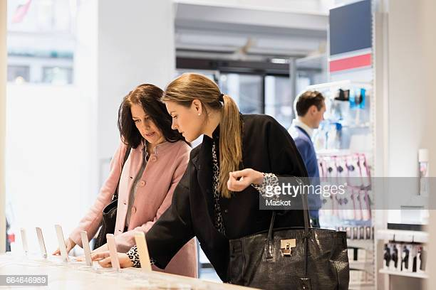 female customers are using smart phones in showroom - electronics store stock photos and pictures