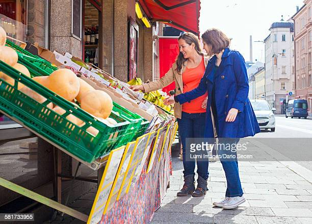 Female customers at greengrocers shop