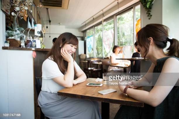 female customers spending relaxing in the afternoon cafe - カフェ ストックフォトと画像