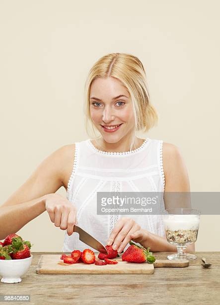 female cutting up strawberries for her breakfast