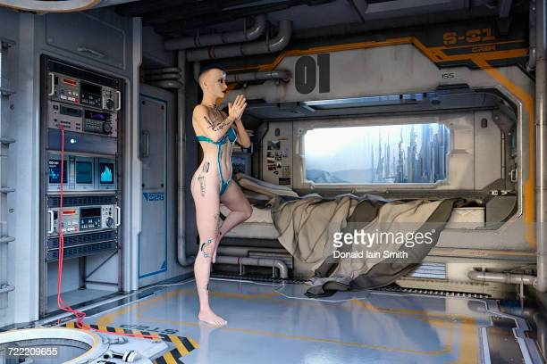 Female cyborg practicing yoga in futuristic bedroom