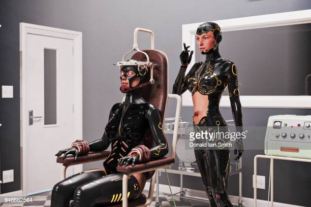 Female cyborg strapped into mind control chair with female cyborg operator standing behind
