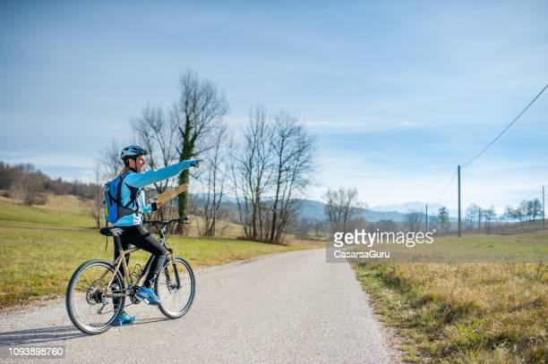 mujer cycler apuntando en dirección cross - país tour - cross country cycling fotografías e imágenes de stock