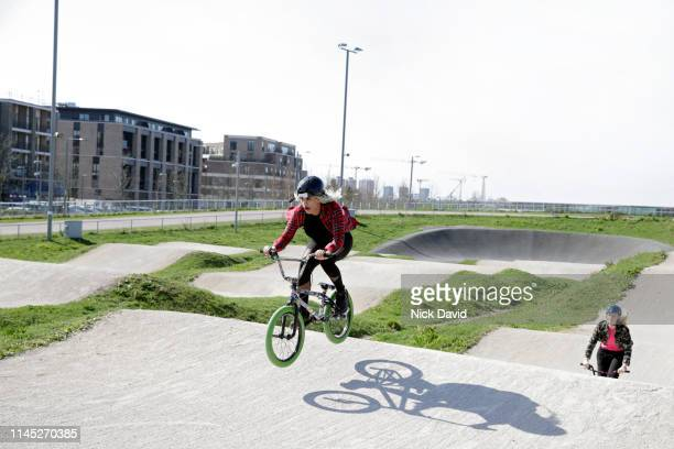 female cyclist beating friend in race on bmx - bmx track london stock pictures, royalty-free photos & images