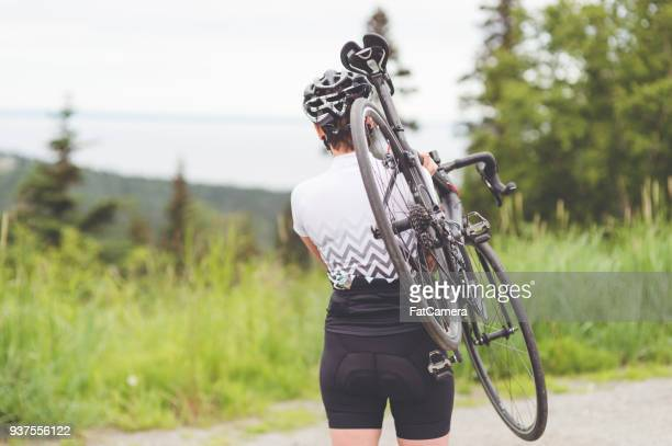 female cyclist carries her bike to the starting point. - road cycling stock pictures, royalty-free photos & images