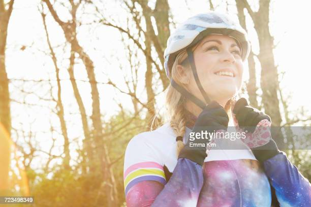 female cyclist fastening helmet in park - crystal palace london stock pictures, royalty-free photos & images