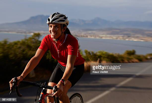 Female cyclist going uphill on roadbike & laughing