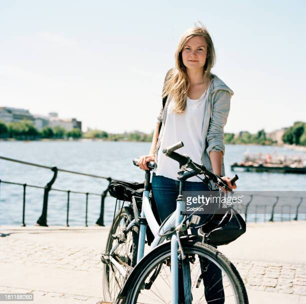 female cyclist in city, lake in the background - una sola mujer joven fotografías e imágenes de stock