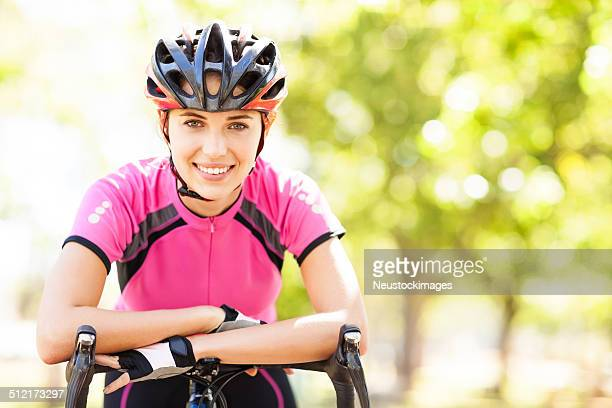 female cyclist leaning on bicycle handlebars - cycling helmet stock photos and pictures