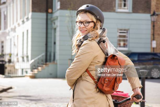female cyclist looks over shoulder, holding her bike in urban street. - cycling helmet stock pictures, royalty-free photos & images