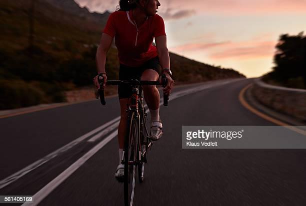 female cyclist on race bike, looking back - dusk dark photos et images de collection