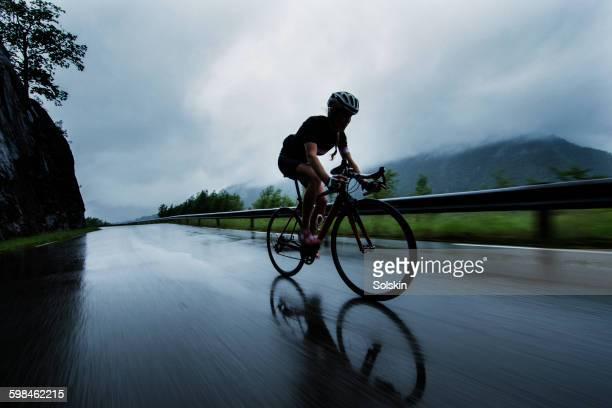 Female cyclist racing down mountain road