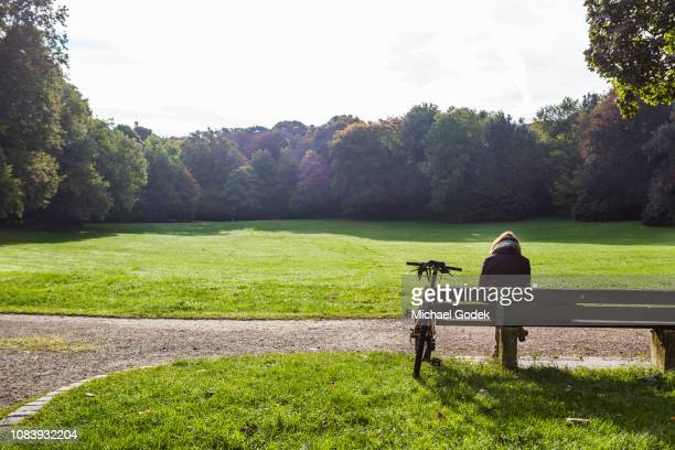 female cyclist relaxing on bench at bavaria park - park bench stock pictures, royalty-free photos & images