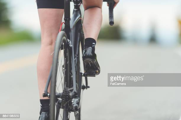 female cyclist rides along a rural highway - road cycling stock pictures, royalty-free photos & images