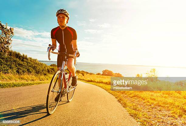 Female cyclist rides bike up a steep hill at sunset