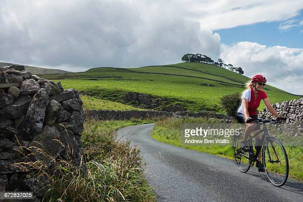 Female cyclist riding through the Yorkshire Dales