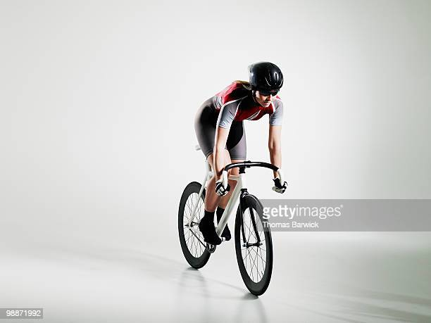 Female cyclist riding track bike