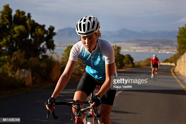 Female cyclist, taking lead on mountain climb
