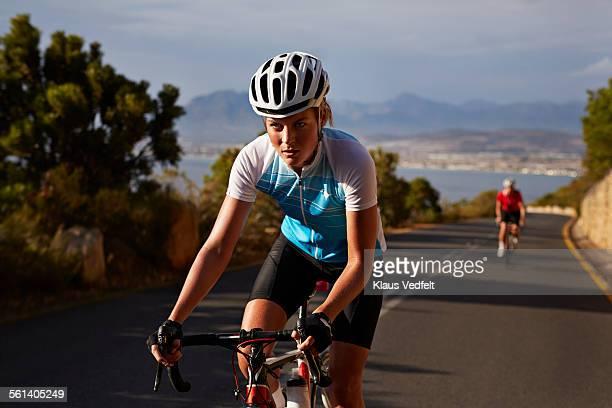 Female cyclist, taking lead on mountain climb