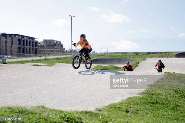 female cyclist wining bmx race on track - bmx track london stock pictures, royalty-free photos & images
