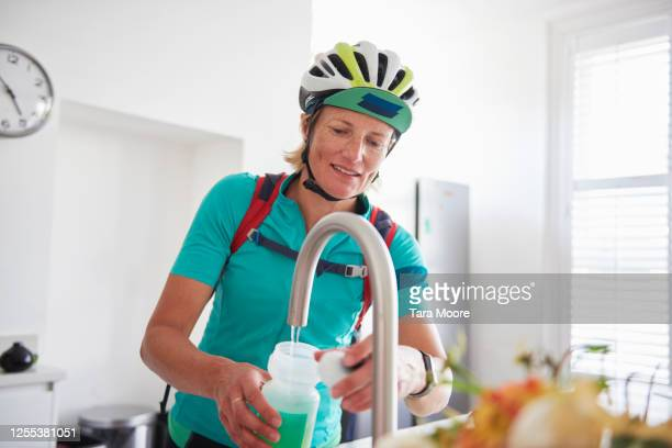 female cyclist with water bottle in house - drinking stock pictures, royalty-free photos & images