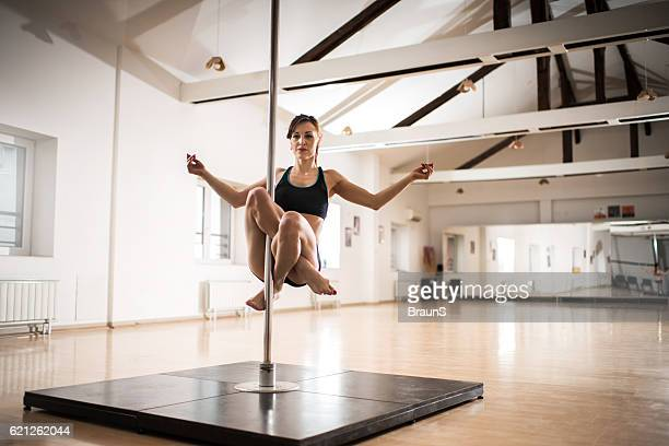 female dancer doing teddy buddha on a dancing pole. - pole dance photos et images de collection