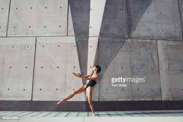 Female dancer in a black leotard dancing in front of a modern concrete building