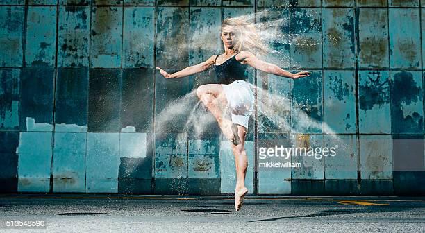 Female dancer jumps through a cloud of flour