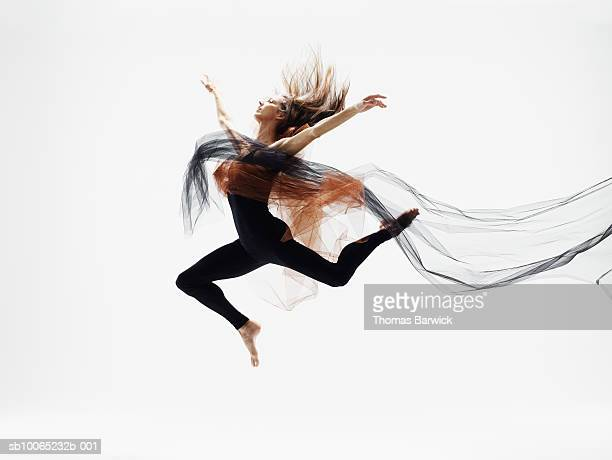 female dancer leaping in mid air against white background, side view - bailar fotografías e imágenes de stock